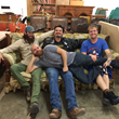 Matthew Wright, Zack Scott, Jonathan Dodd, and Michael Arneel (across), feature film art crew, relax a moment during shooting at Squash Blossom Studios in Dallas.