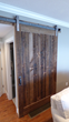 As-found brown board and brushed nickel hardware come together to form this Flat Track Door recently installed to separate a family room from the hallway in a NY home.