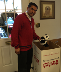 "Dan Buan, CEO of Buan Consulting making a donation to ""Toys for Tots."""