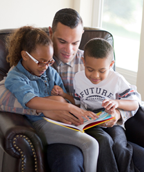Parent reading with his children.