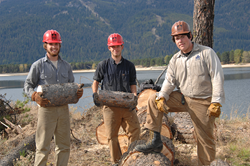 Three young men stand with logs in front of Lake Cascade Reservoir.