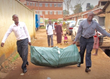 Relief Beds being carried into the Slum in Bwaise by volunteers.