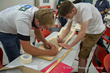 Students Cooper Winrich and Chris Tombstone work on their boards in a recent skateboard build class partnered with TALK.