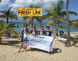 Team members sponsored by Cane Bay Partners VI, LLLP  include St. Croix residents (left to right) Colleen Chin, Robin Seila, Esther Ellis and Julie Sommer pose by the finish line on Mermaid Beach at The Buccaneer.