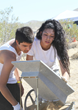 Young prospectors operate a drywasher as they prospect for gold in the desert.