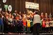 Students sing a happy kindness song at school-wide assemblies.