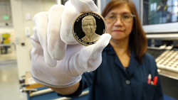 Teresita Gatmaitan, a die setter at the United States Mint at San Francisco, holds a finished 2016 Ronald Reagan Presidential $1 coin. U.S. Mint photo by Adam Stump.