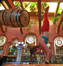 While doing a handstand on the bar at El Pinto Restaurant in Albuquerque, NM, YogaRita Guru Sydney Fontaine Forestal drinks a YogaRita margarita in celebration of National Margarita Day.