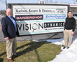Scott Krug and Charlie Collins stand in front of the Vision Dynamics sign (Vision Dynamics was just acquired by New England Low Vision and Blindness)