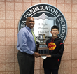 Ethan presents trophy to Head of School Kevin Plummer.