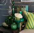 Luscious verdant glass goods surround silk pillows by Alexandra Foster.