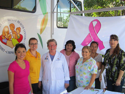 La Maestra's imaging and health education staff stand in circle in front of mobile unit, pink ribbon in background.