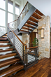 "The main staircase features 3.5""-thick walnut slab treads, as well as walnut rails mounted atop square steel newel posts and horizontal balusters."