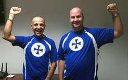 Cane Bay Partners Chief Risk Officer Mehran Chirehdast and Software Development Manager Jeff Dykstra try on the athletic shirts freshly made for their upcoming participation in the Ironman 70.3 Triathlon under the Team Cane Bay VI banner.