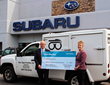 Robert J Alvine, President, Premier Subaru Watertown presents Lisa LaBonte, Program Director, New Opportunites with a check for more than $19,000.