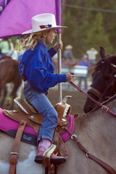 young cowgirl riding a horse and carrying a flag