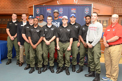 Nine cadets made commitments to play for college programs this coming year, shown here flanked by Academy President RADM J. Scott Burhoe (second from left) and Athletic Director Micky Sullivan (at right). Cadet Michael Harper (at left) made his commitment