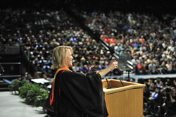 Commencement keynote speaker Gretchen McClain takes a selfie on stage at the Maverik Center in West Valley City.