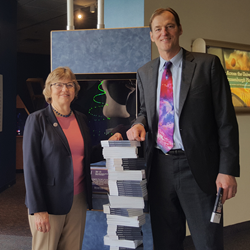 "Rochester Museum & Science Center President Kate Bennett accepts 400 copies of ""Photonics Infographics"" from Peter Hallett of SPIE, the international society for optics and photonics."