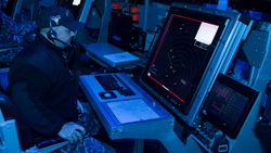 Chief Air Traffic Controller Keith Thompson demonstrates the first air traffic control simulator installed on board the aircraft carrier USS Carl Vinson