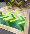 Shades of green and natural patinated wood surfaces come together in a shattered herringbone pattern that ICFF attendees can see and feel May 14 – 17 in Pioneer Millworks booth #2520.