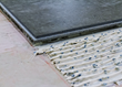 Couse up view of the tongue-and-groove edge of a Concreate plank, with fresh adheisve applied to the floor alongside it.  The white adhesive paste has visible black grains of rubber scattered through it.