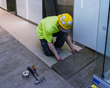 A worker installs a fresh row of Concreate planks, next to a row already installed.