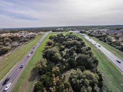 "South Mopac looking south at the Slaughter Lane intersection.  The 2.1 mile ""Mopac Intersections"" piece of the 17-mile tolled loop would add six freeway lanes within the green median shown above, 3 new lanes in each direction."