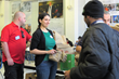 Pharmachem volunteers hand out lunch bags at Eva's Community Kitchen, which provides nearly 400 meals a day to guests in the Paterson community..