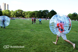 A bubbleball encased bubble soccer player hurtles towards his opponent.