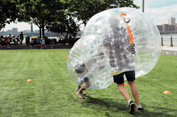 Two bubbleballs collide in a smashing game of bubble soccer.