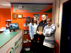 Minuteman Press franchise owner Joe McLaughlin (middle) along with his wife Florina (right) and graphic designer Samantha (left)