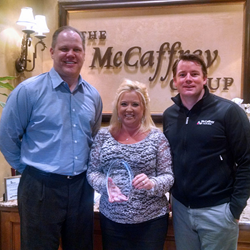 Brent McCaffrey and Ash Knowlton of McCaffrey Homes present honor Janel Showers for ten years of service to McCaffrey Homes