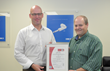 LINAK U.S. Director of Quality Doug Clark, left, and Quality Management Systems Coordinator Doug Phelps, right, pose with the official LINAK U.S. ISO 14001:2004 certification document.