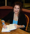 "Mara Purl signs her novel ""Where the Heart Lives"""