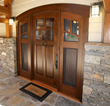 The entry to this LEED-H Gold home is a NEWwoodworks custom-crafted curved walnut door, double the usual thickness to better fit two screened and glass filled sidelights.
