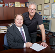 CRL's Jay Brentlinger and DaySequerra's David Day sign the acquisition agreement at CRL headquarters.