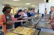 Volunteers from Rapid Pump and Meter Co., gold-level Fund-A-Meal sponsor, help to serve a hot lunch to 400 guests at Eva's Village Community Kitchen.
