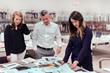 FSU graduate & Pineapple House senior designer Zach Azpeitia is shown with designers Kate Fleming and Katie Moorhouse in the Pineapple House library.