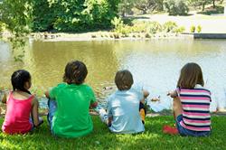 Children sitting by waterr on the grass.