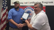 Marcus Irvine accepts the EF16@IWCE Veteran scholarship from Veterans Assembled electronics CEO John Shepard.