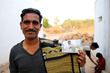 Artisan, Premji in Bhuj, India shown here holding an Ethnotek Thread panel that features his handmade fabric.