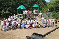 Volunteers pose for a group photo during playground build