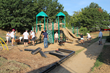 Volunteers spread surfacing material around playground