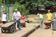 Volunteers move surfacing material around playground site