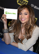 Jennifer Lopez holding a Masters of Money logo sign.