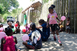 Sandrins plays Duck, Duck, Goose with Mercy Ships staff and her friends.