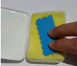 This sponge is filled with glue and an object is pressed onto it to push the glue out.
