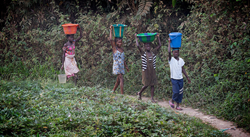 Children carry water from a community water source outside Bo, Sierra Leone. Photo by Mike DuBose, UMNS