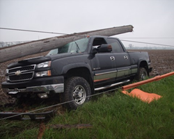 Truck wreck with a power pole and downed lines